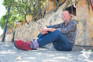 • Fremantle councillor Andrew Sullivan shelters from the summer heat under the frangipani trees of the warders cottages and ponders their future. Photo by Steve Grant