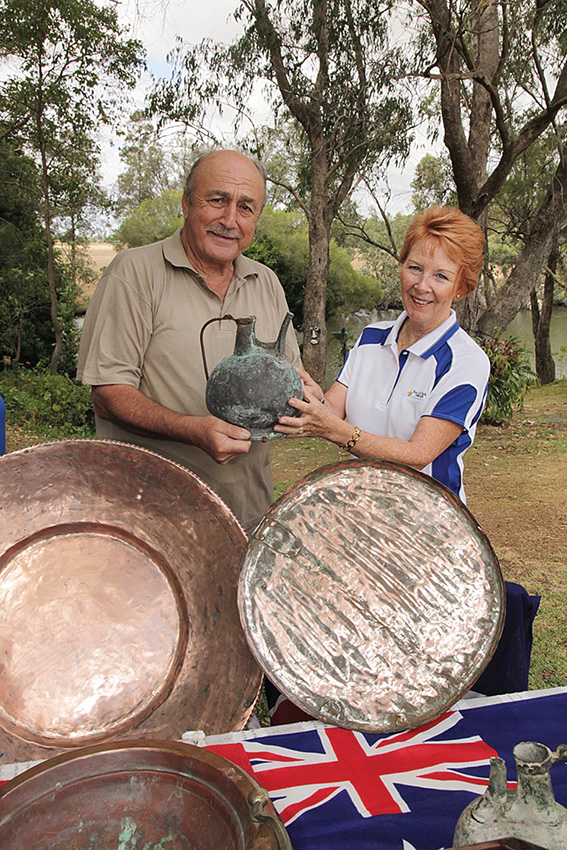 • Demir Bükey presents a copper jug from Gallipoli to Blue Gum tennis club president, Pauline Foster, with his own collection of bullets, shrapnel and other war relics from the Gallipoli peninsula in the foreground.