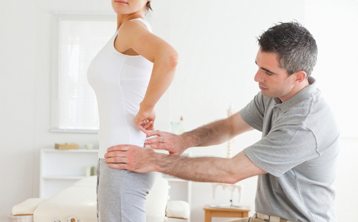 Chiropractor examining a charming woman's back in a room
