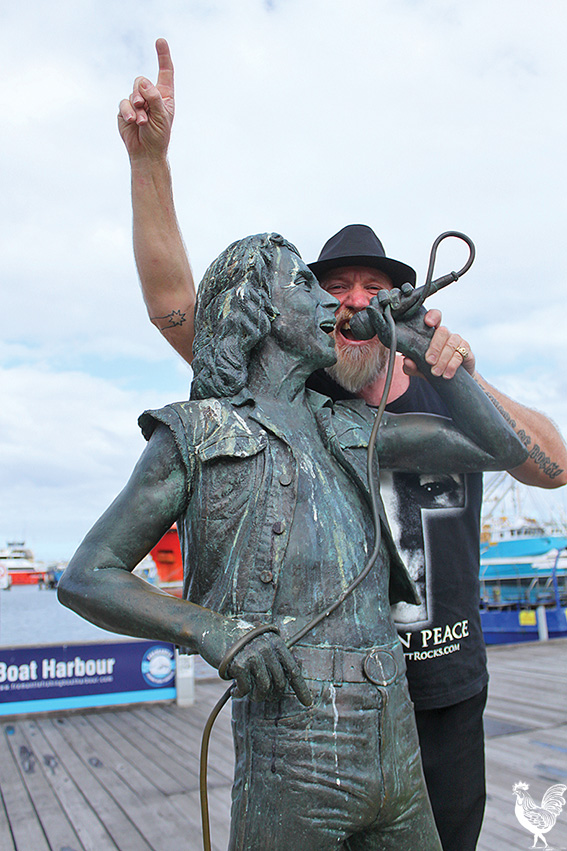 • Doug Thorncroft on the Bon Scott statue in Fremantle. Photo by Stephen Pollock