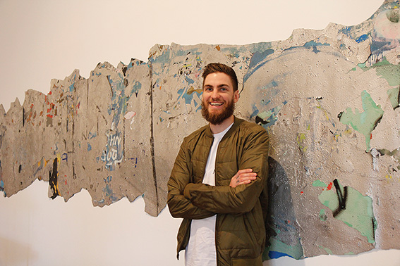 • Sam Bloor and his award-winning print, peeled off a favourite haunt of graffiti artists. Photosupplied